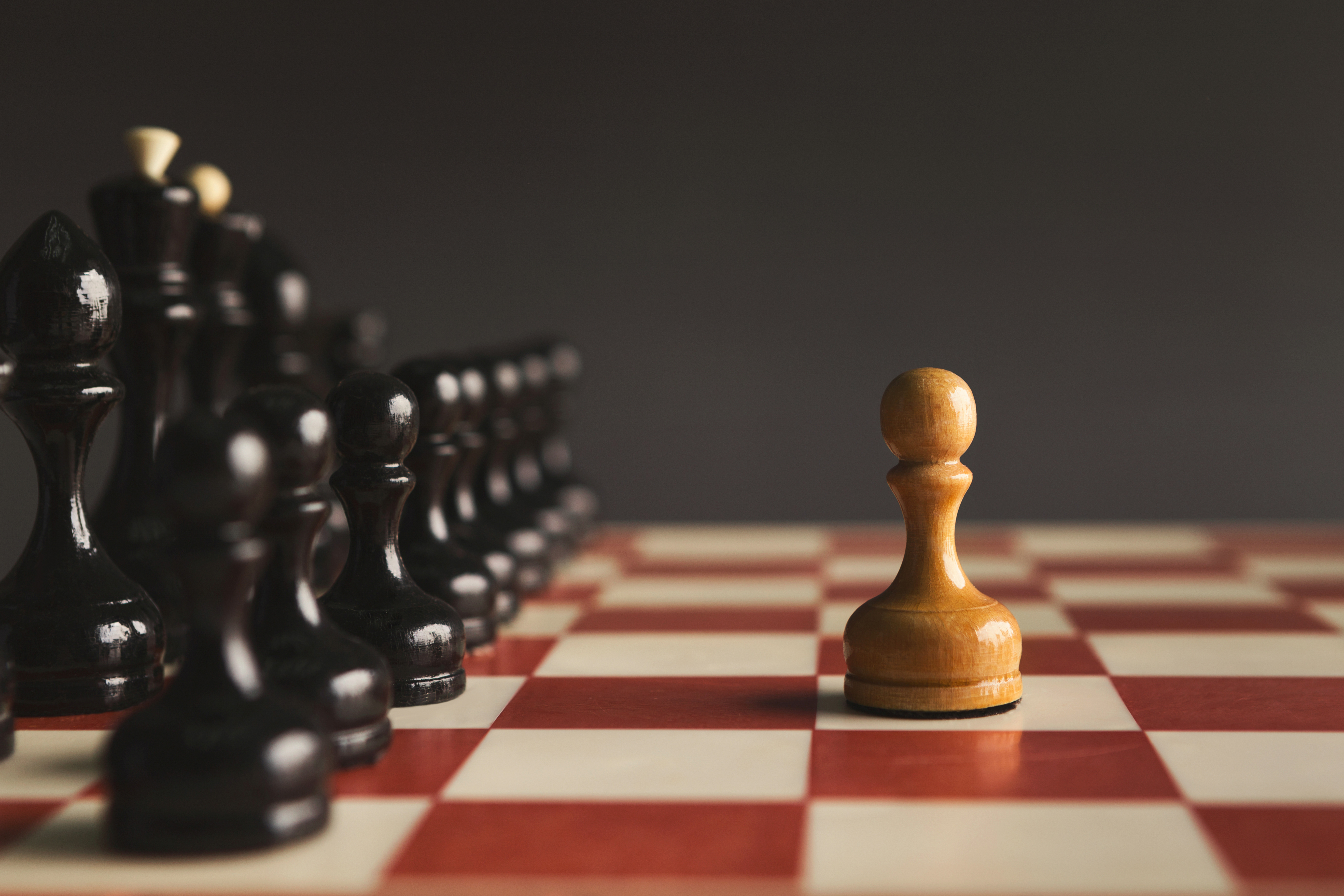 bigstock-One-Pawn-Standing-Against-Set--386213593