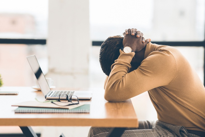 Employee with head down at his desk