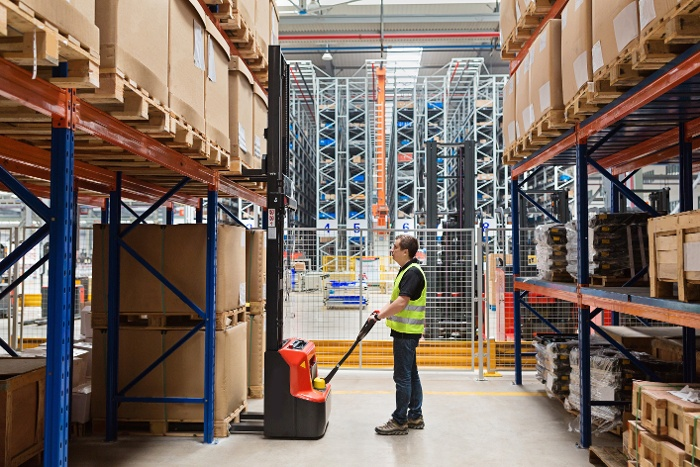 male opperating a forklift in a large warehouse